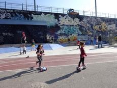 Kinder auf Rollern im Hof vor einem Graffity